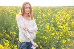 Pollen allergy, girl sneezing in a rapeseed field of flowers.  Royalty Free Stock Photos