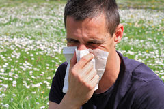 Pollen allergy, Springtime. Man sneezing in a tissue Royalty Free Stock Photo