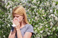 Pollen allergy, Springtime. Woman sneezing in a tissue Royalty Free Stock Photo