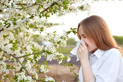 Pollen allergy symptom. Sideways outdoor shot of young European female sneezes in handkerchief or blows in wipe , being allergic t. O blossom during spring Royalty Free Stock Photography
