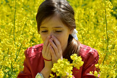 Pollen allergy. Teenage  girl has hay fever, sneezing in a field of canola  flowers Stock Photos