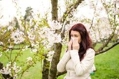 Pollen allergy. A woman sneezing because of pollen allergy in a garden in the spring stock photo