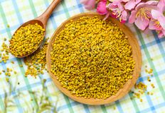 Pollen d'abeille dans le plat et la cuillère en bois image stock