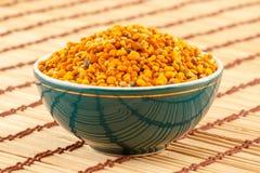Pollen granules in bowl. Pollen granules in green porcelain bowl on light rustic mat stock photo