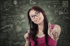 Pollice attraente di manifestazione della studentessa su nella classe Fotografia Stock Libera da Diritti
