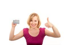 Pollice della giovane donna alto e che presenta la carta di credito Immagini Stock Libere da Diritti