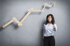 Pollice grazioso della tenuta della donna di affari su davanti al grafico positivo di affari Fotografia Stock Libera da Diritti