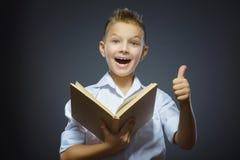 Pollice sorridente bello di manifestazione del ragazzino su e libro olding isolato su fondo grigio Immagini Stock Libere da Diritti