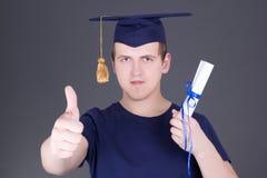 Uomo di graduazione con i pollici del diploma su sopra grey Fotografia Stock Libera da Diritti