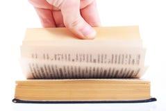 Pollici della mano attraverso il libro. Isolato Immagini Stock Libere da Diritti