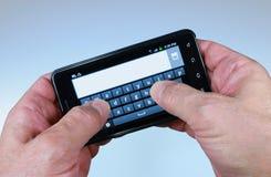 Pollici di Texting su Smartphone Fotografie Stock