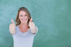 Pollici diritti sorridenti dell'insegnante su davanti alla lavagna Immagini Stock Libere da Diritti