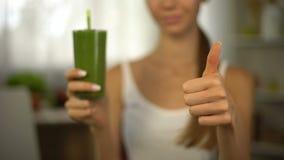 Pollici esili della ragazza su, tenendo frullato verde per perdita di peso, dieta sana stock footage