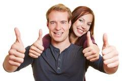Pollici felici della tenuta delle coppie del vincitore Immagine Stock