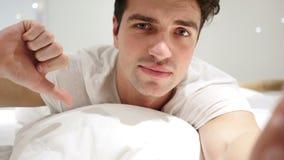 Pollici giù dall'uomo che si trova a letto sullo stomaco, aborrente stock footage