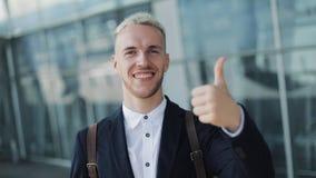 Pollici su dal giovane uomo d'affari attraente fuori dell'ufficio Condizione felice dell'uomo vicino all'aeroporto e esaminare la archivi video