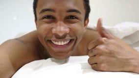 Pollici su dall'uomo africano felice che si trova a letto sullo stomaco video d archivio