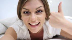Pollici su dalla donna felice che si trova a letto sullo stomaco video d archivio