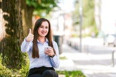 Pollici su dalla giovane bella donna di affari che utilizzano il cellulare all'aperto fotografia stock