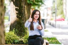 Pollici su dalla giovane bella donna di affari che utilizzano il cellulare all'aperto fotografia stock libera da diritti