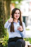 Pollici su dalla giovane bella donna di affari che utilizzano il cellulare all'aperto fotografie stock libere da diritti