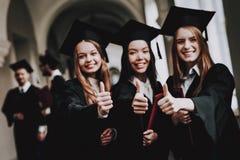 Pollici in su diploma ragazze cheerful protezione felice immagine stock libera da diritti