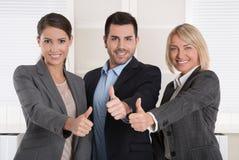 Pollici su: tre riuscite genti di affari dell'uomo e della donna dentro immagini stock