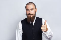 Pollici in su Uomo d'affari bello con i baffi del manubrio e della barba che esaminano macchina fotografica con i pollici su Fotografia Stock