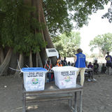 Polling station and ballot boxes. Polling station, ballot boxes and international election observer in rural Guinea-Bissau during general elections in 2014 stock image