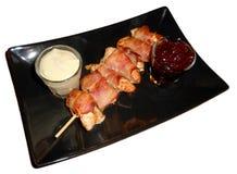 Pollo acciambellato con bacon e salse isolati su bianco Fotografia Stock Libera da Diritti