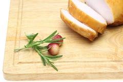 Pollo affumicato su un tagliere con il mirtillo rosso ed i rosmarini Fotografia Stock