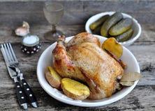Pollo arrostito con la patata al forno su una tavola di legno Fotografia Stock