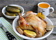 Pollo arrostito con la patata al forno su una tavola di legno Fotografie Stock Libere da Diritti