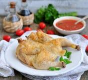 Pollo arrostito con una salsa al pomodoro su una tavola di legno Immagine Stock