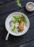 Pollo, arroz y ensalada cocidos en un cuenco en un fondo de madera oscuro foto de archivo