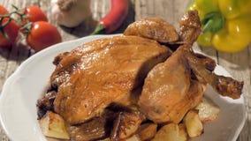 Pollo asado con las patatas cocidas en la placa blanca que gira