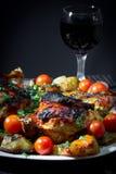 Pollo asado con las patatas y los tomates de cereza fritos. Fotografía de archivo