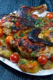Pollo asado con las patatas y los tomates de cereza fritos. Foto de archivo libre de regalías