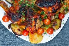 Pollo asado con las patatas y los tomates de cereza fritos. Imagen de archivo