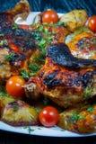 Pollo asado con las patatas y los tomates de cereza fritos. Imagen de archivo libre de regalías