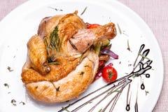 Pollo asado con romero en una placa blanca Fotografía de archivo