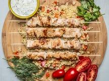 Pollo asado en la salsa del pincho con las hierbas y los tomates en una tabla de cortar en un cierre de madera azul de la opinión fotografía de archivo