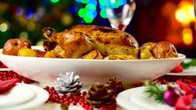 Pollo asado en la tabla de la Navidad delante de la chimenea y árbol con las luces almacen de metraje de vídeo