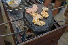 Pollo asado a la parrilla frito en una roca natural Carne deliciosa foto de archivo