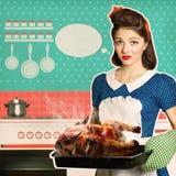 Pollo asado pasado por alto de la mujer joven en un horno Fotografía de archivo libre de regalías