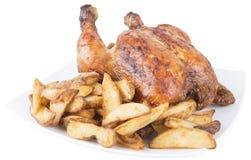 Pollo asado y patatas fritas en el plato blanco Aislado en blanco Foto de archivo