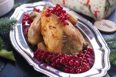 Pollo cocido en un disco con las bayas rojas en una tabla de madera azul con un rastrillo Fotos de archivo