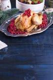 Pollo cocido en un disco con las bayas rojas en una tabla de madera azul con un rastrillo Imagen de archivo libre de regalías