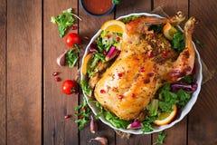 Pollo cocido relleno con el arroz para la cena de la Navidad en una tabla festiva Imagen de archivo