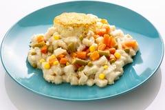 Pollo con verduras mezcladas y una galleta en una placa azul que se sienta en una tabla de cocina blanca que espera para ser comi foto de archivo libre de regalías